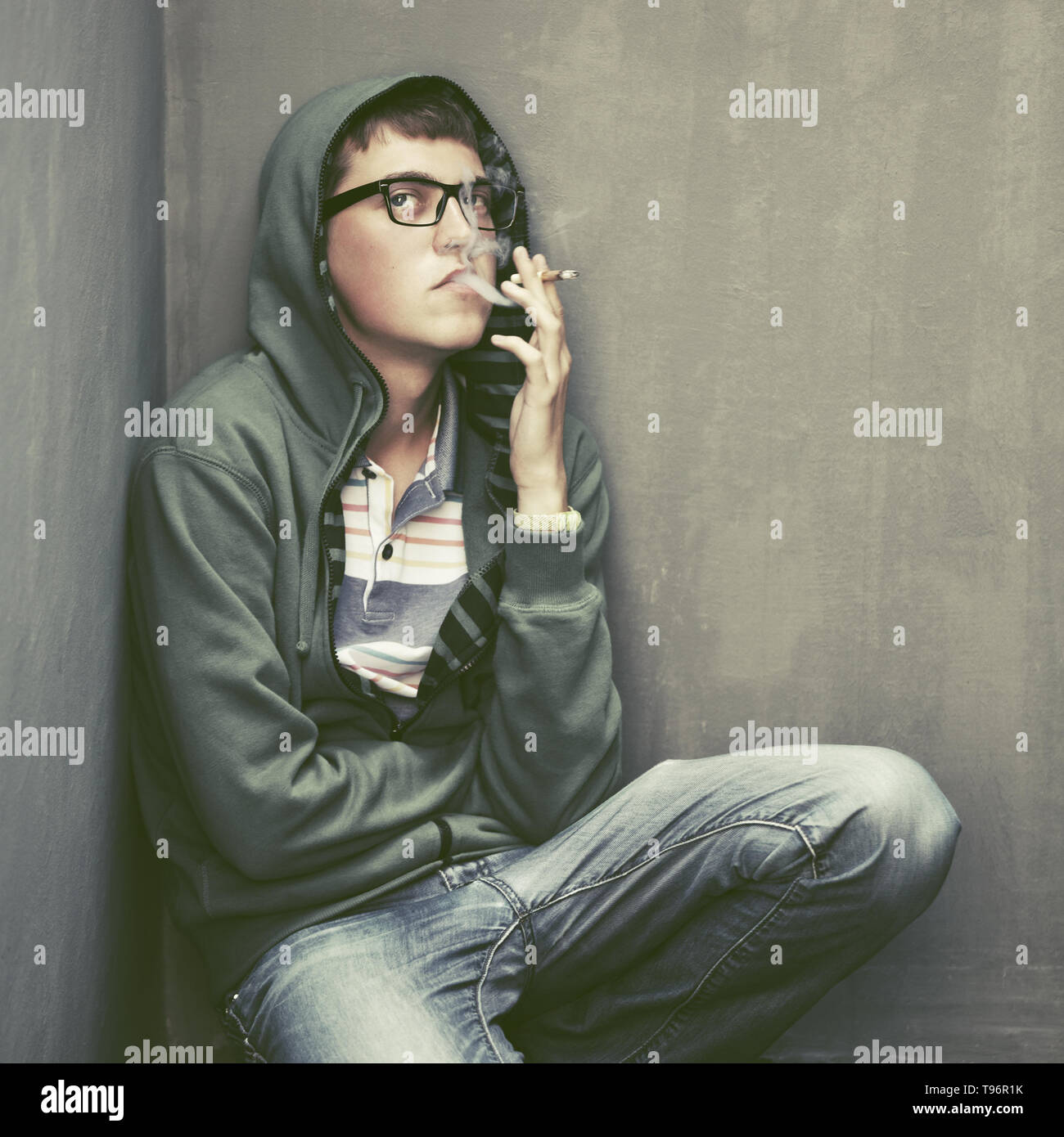 Sad teen boy in a hooded jacket smoking cigarette at the wall