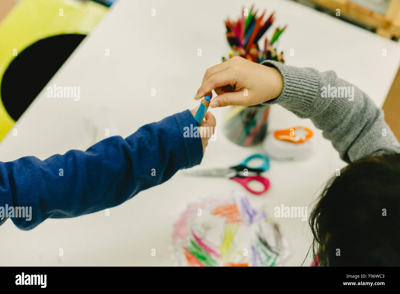 Two students share pencils in a nursery school, concept of collaboration - Stock Image