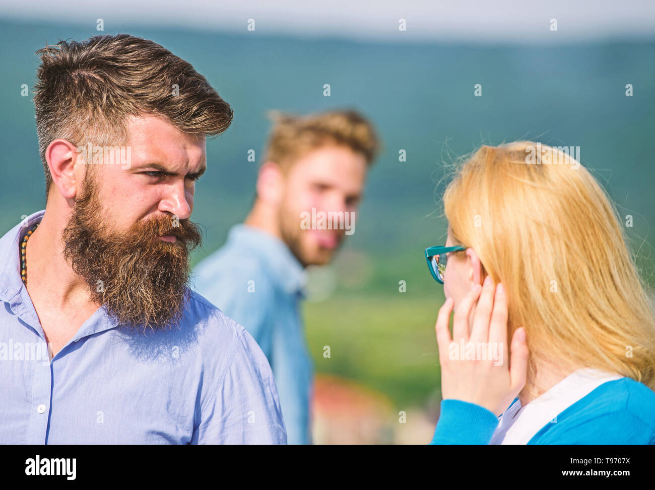 Husband strictly watching his wife looking at another guy while walk. Jealous concept. Passerby smiling to lady. Man with beard jealous aggressive because girlfriend interested in handsome passerby. - Stock Image