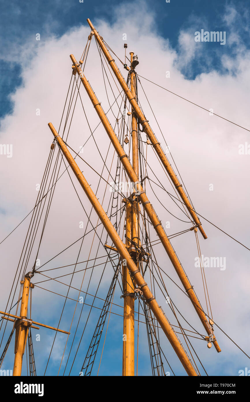 Ships mast and rope on a cloudy sky background. - Stock Image