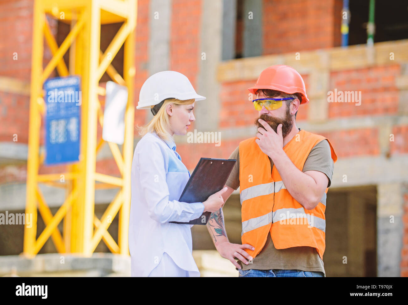 Construction project management. Building industrial project. Construction industry concept. Discuss progress project. Woman engineer and bearded brutal builder discuss construction progress. - Stock Image