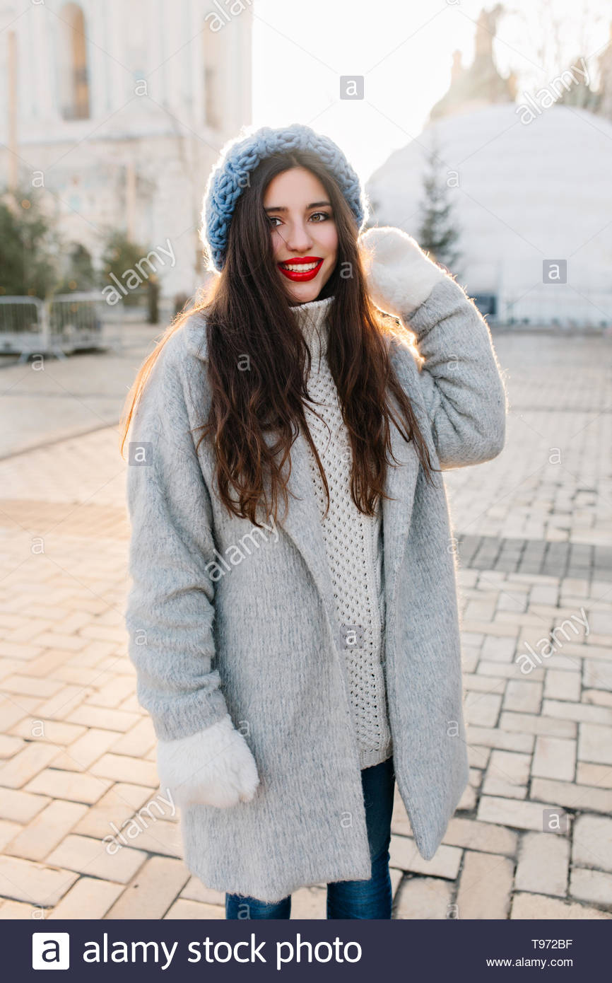 Pretty brunette girl in blue hat and gray coat standing on the street on blur background and smiling. Outdoor photo of gorgeous female model with dark-brown curly hair exploring city in winter. - Stock Image