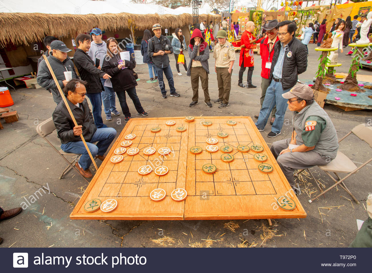 Vietnamese American men play a giant-size chess game at a Tet Lunar New Year festival in Costa Nesa, CA, as Boy Scouts watch. - Stock Image