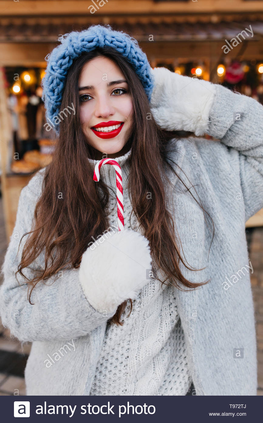 d6ac3899933 Close-up portrait of romantic european girl with dark hair posing with  sweet christmas lollipop