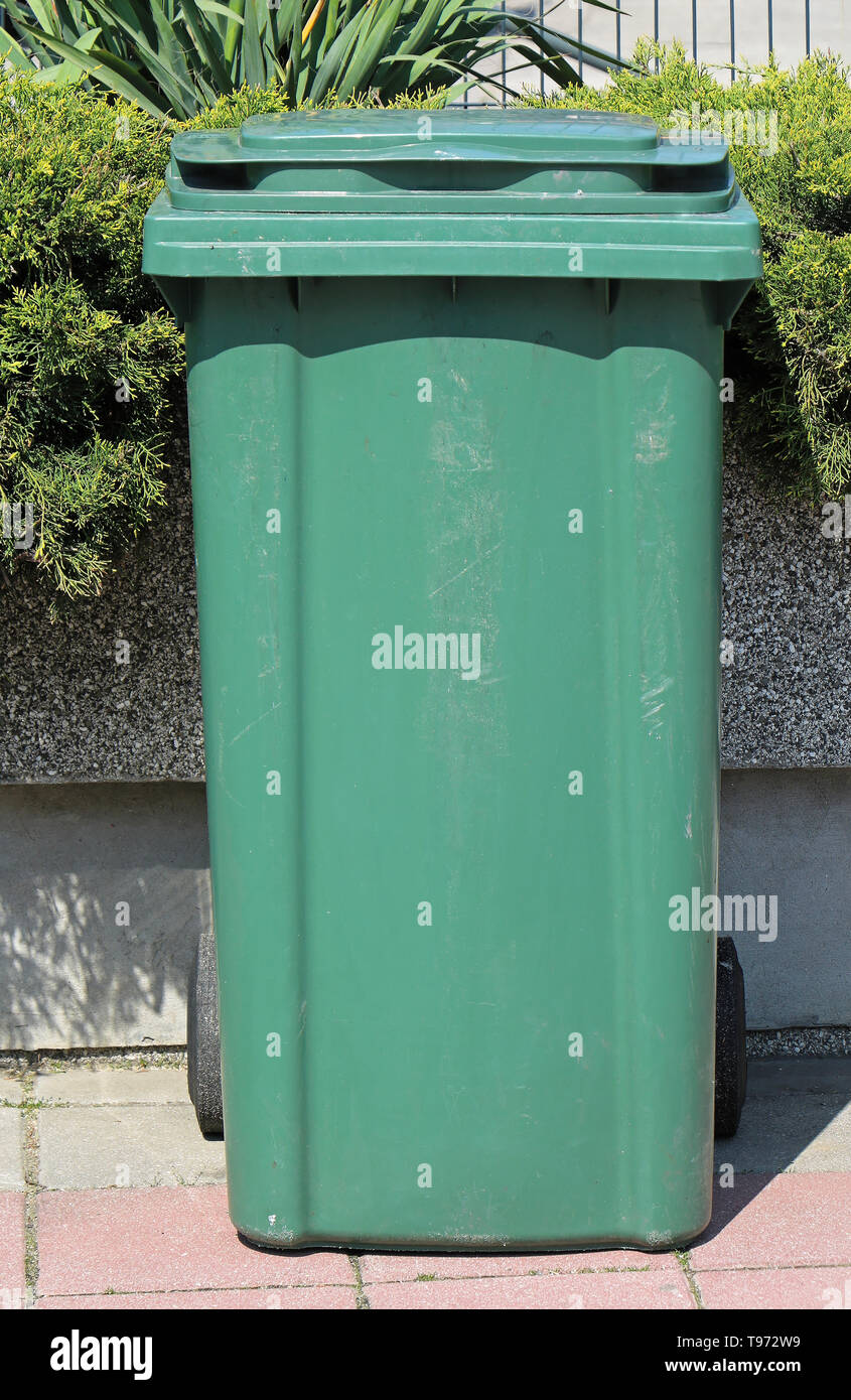 Large closed green plastic trash can outside in park - Stock Image
