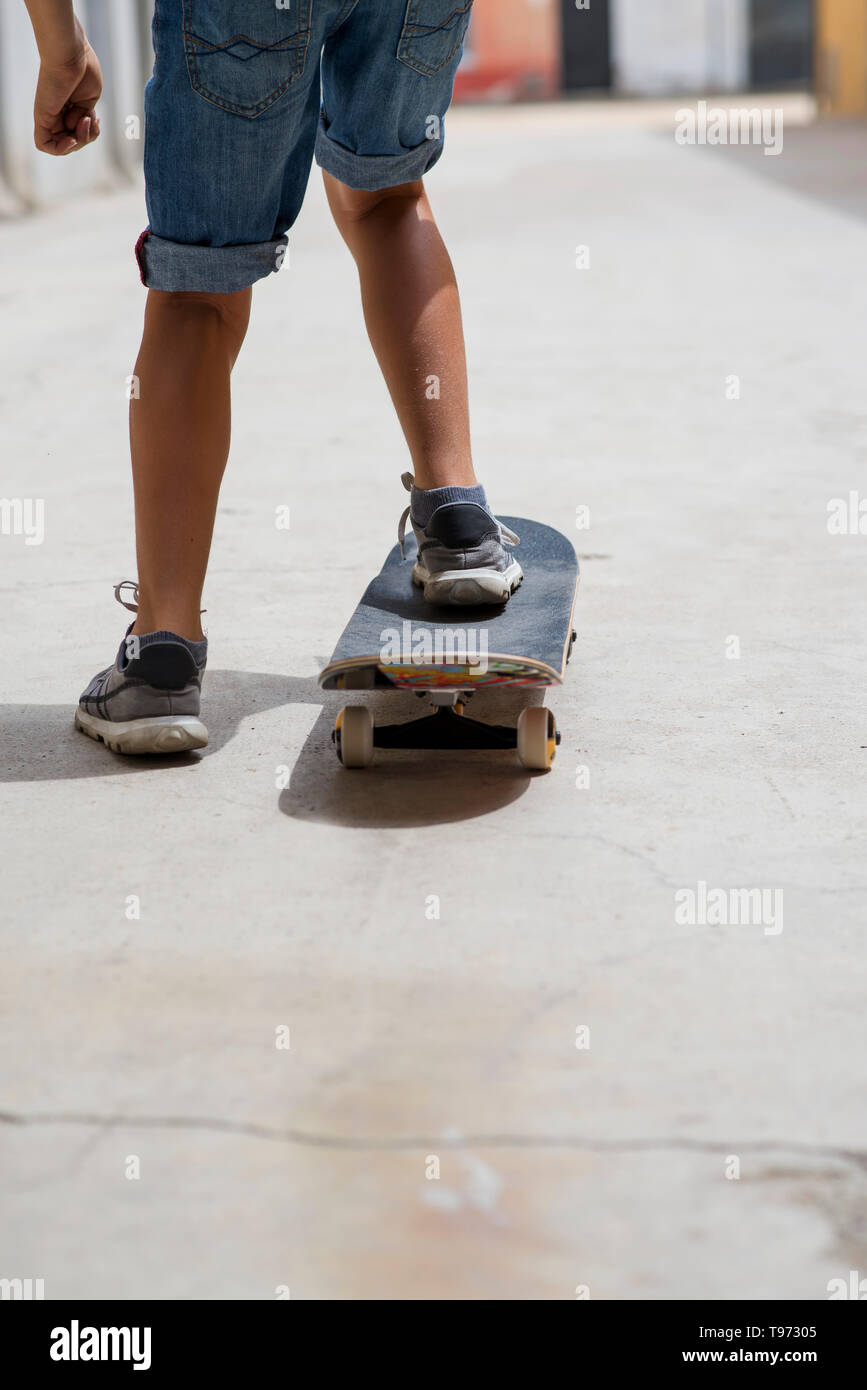 Rear view of a young skateboarder legs riding on skateboard - Stock Image