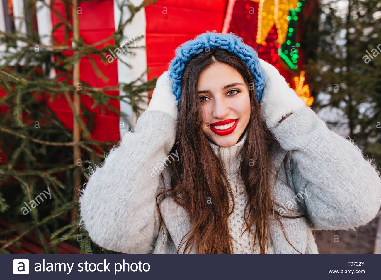 Close-up portrait of enthusiastic girl in blue hat posing with happy face expression in front of christmas trees. Outdoor photo of glamorous woman with  dark hair standing near new year decoration. - Stock Image