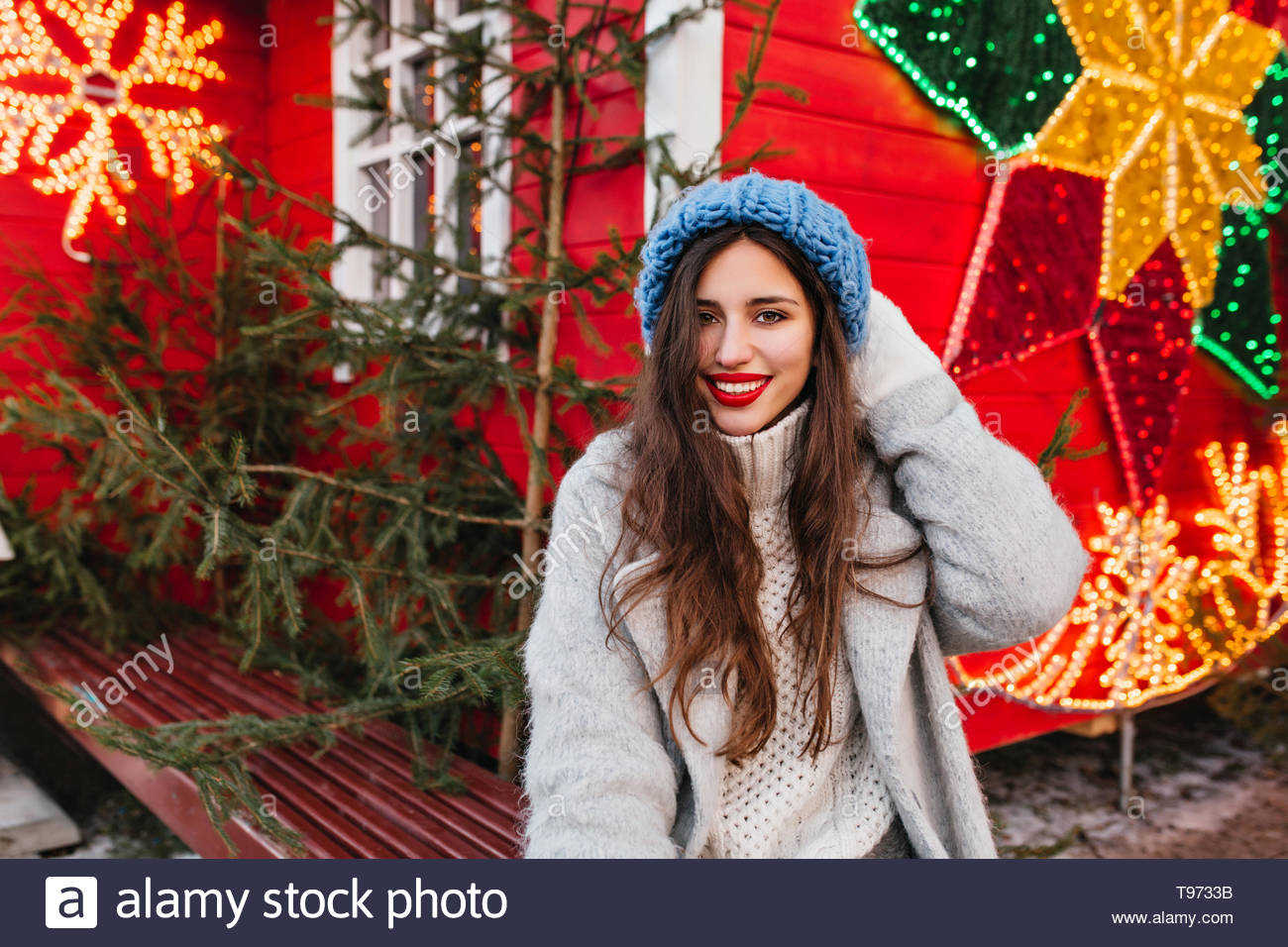 Shy woman with long brown hair spending time on new year fair and posing near green trees. Outdoor photo of spectacular caucasian lady in gray coat standing on red christmas background. - Stock Image