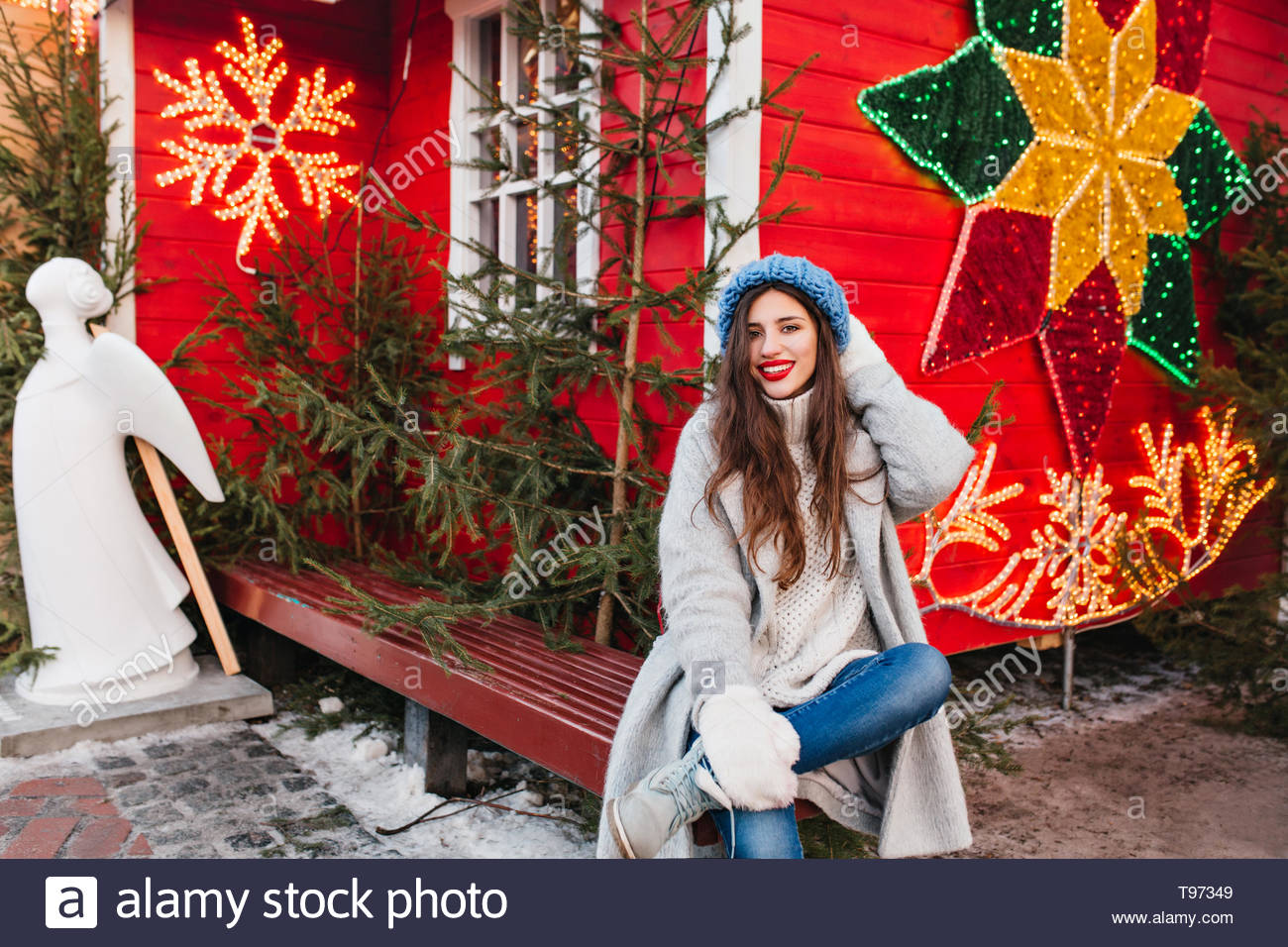 Long-haired female model sits on wooden bench near red house decorated for christmas. Attractive brunette girl posing after new year holiday beside green trees and angel sculptures. - Stock Image