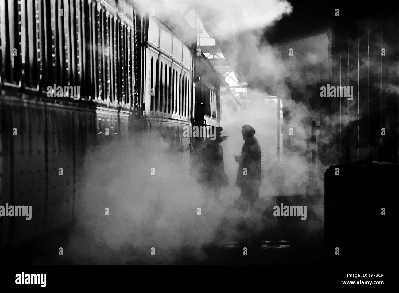 Silhouetted against steam on a cold winter afternoon, a train passenger asks directions at South Station in Boston, MA. - Stock Image