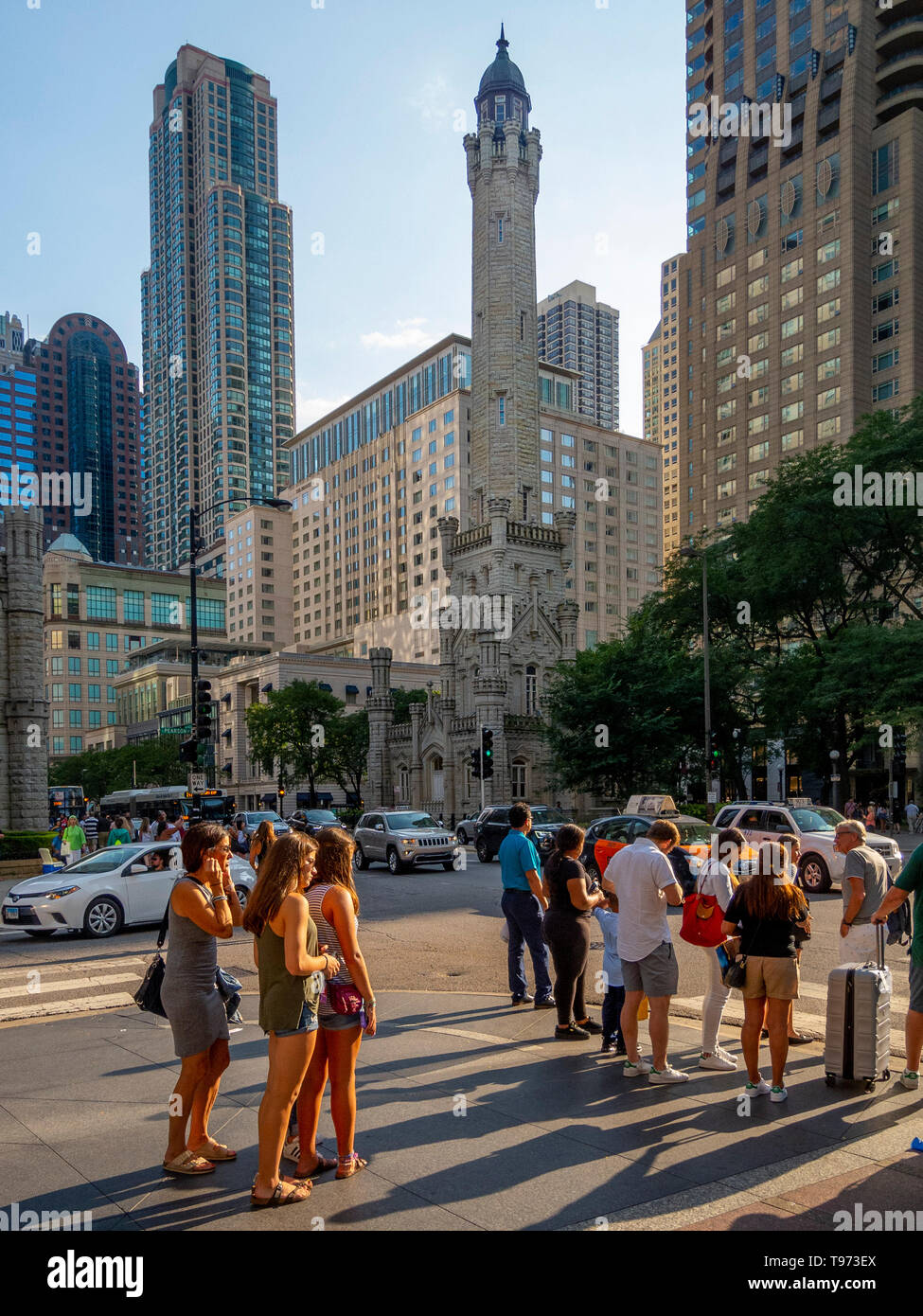 Afternoon sun shines on passersby beside the Chicago Water Tower at 806 North Michigan Avenue along the Magnificent Mile shopping district in the Near North Side community area of Chicago, IL. The tower was constructed to house a large water pump, intended to draw water from Lake Michigan. Built in 1869, it is the second-oldest water tower in the United States. - Stock Image