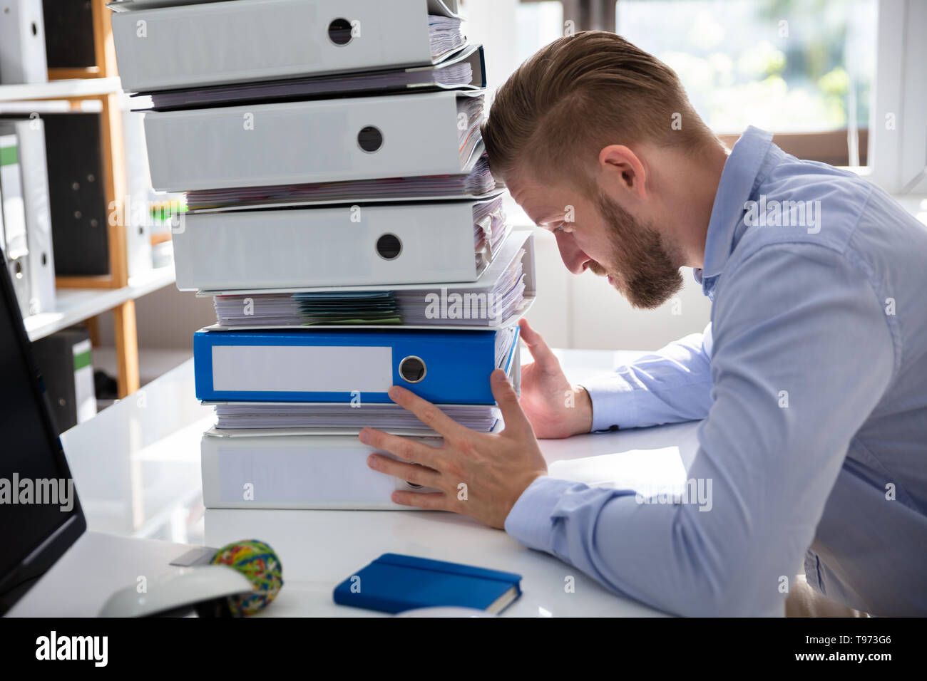 Stressed Businessman Looking At Folders While Working At Desk - Stock Image