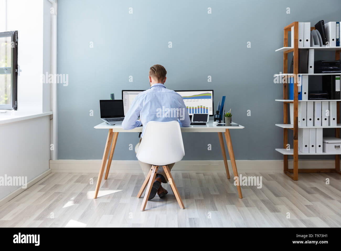 Rear View Of A Businessman Working On Desktop Computer In Office - Stock Image
