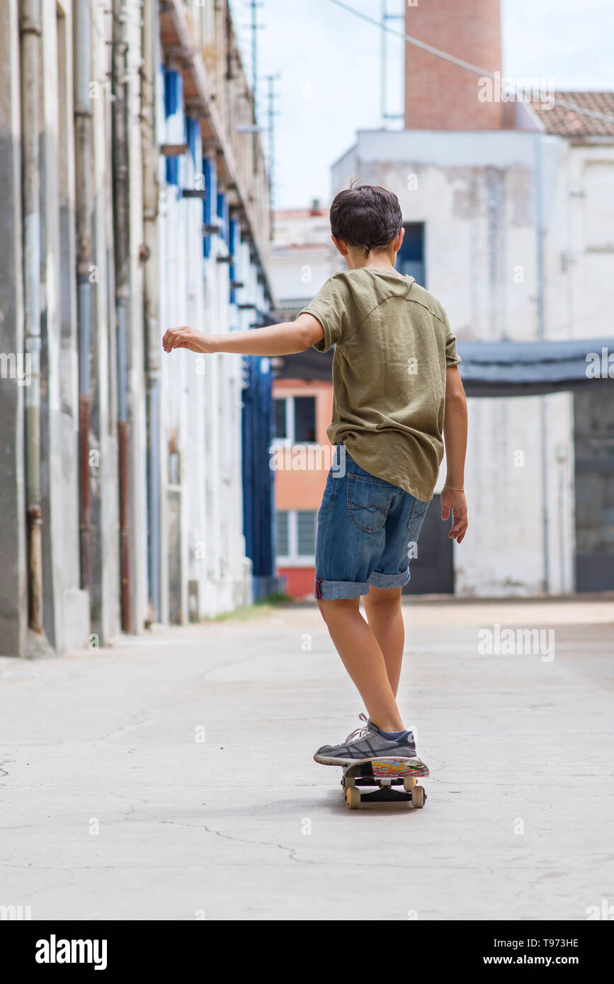 Front view of a cheerful skater boy riding on the city in a sunny day - Stock Image