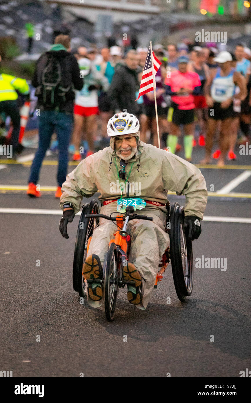 Riding a bicycle wheelchair, a determined 80-year-old man participates in a half marathon foot race in Huntington Beach, CA. - Stock Image