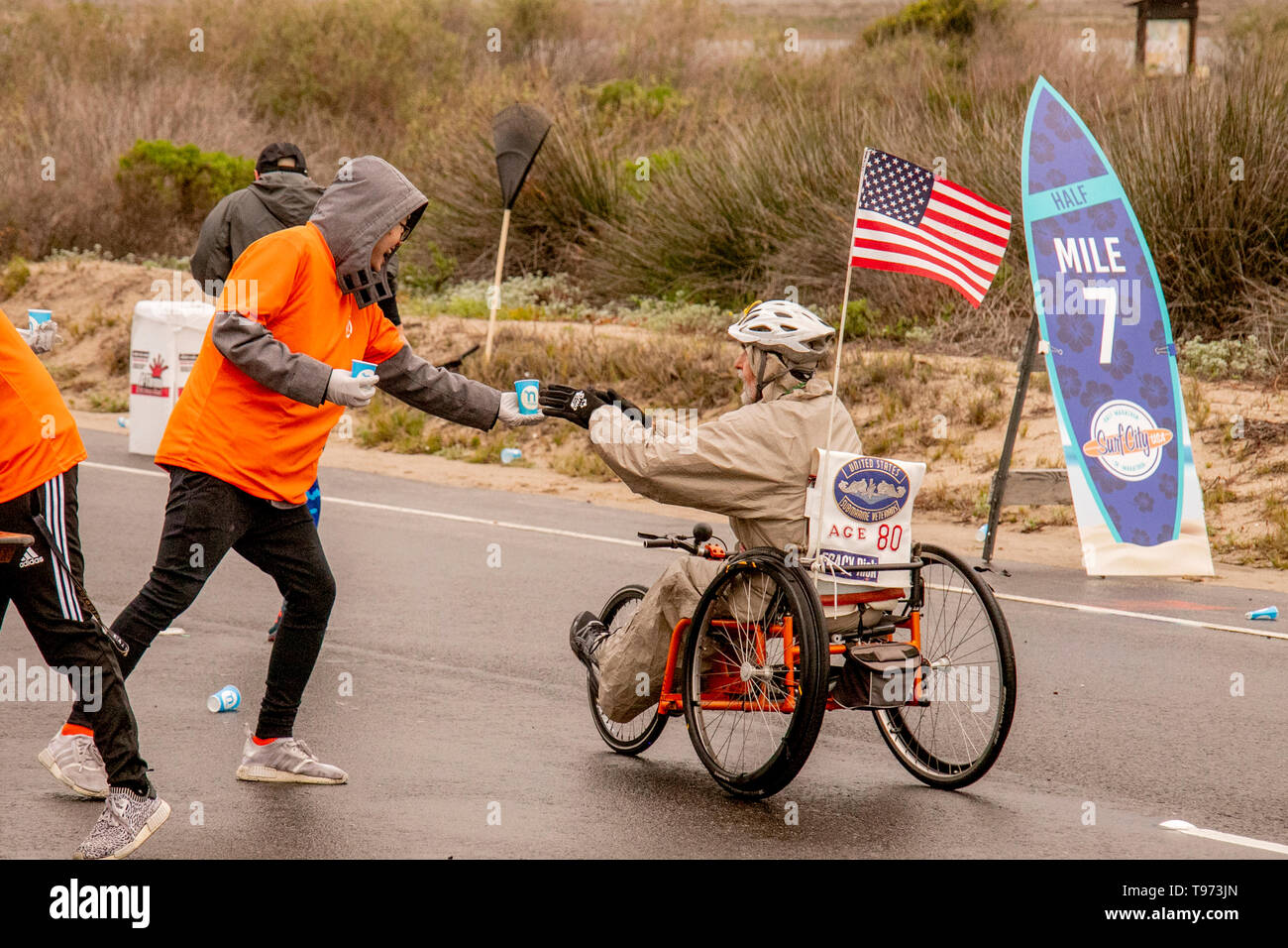 Riding a bicycle wheelchair, a determined 80-year-old man participates in a half marathon foot race in Huntington Beach, CA, as he reaches for a cup of water. - Stock Image