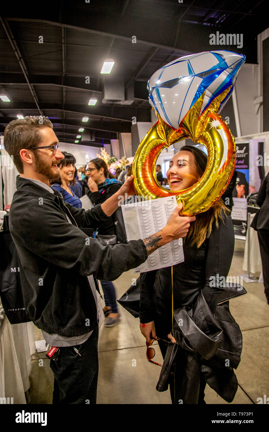 A couple celebrate their engagement with a giant inflatable engagement ring at a bridal fair in Costa Mesa, CA. - Stock Image