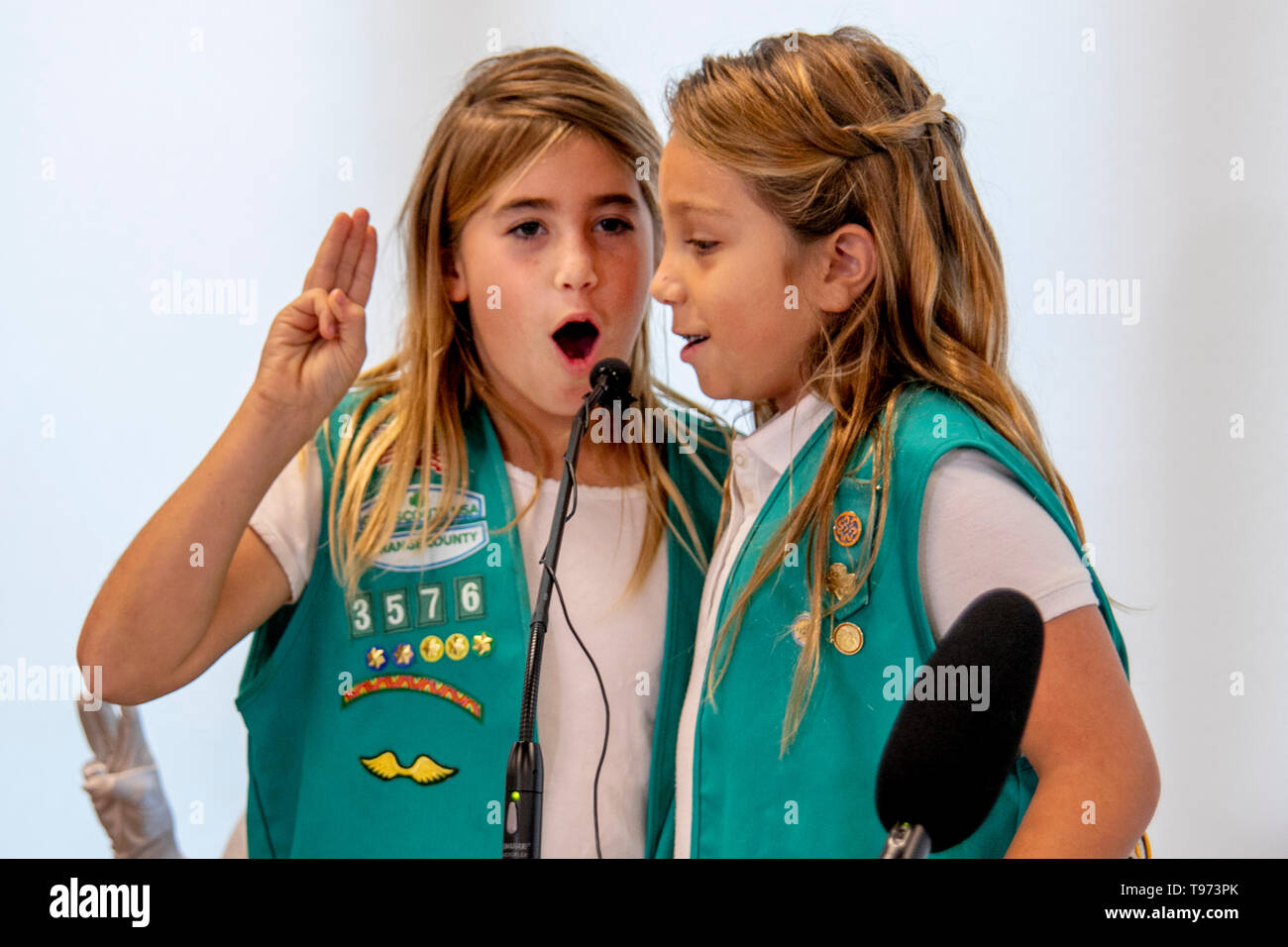 Two uniformed Girl Scouts recite the Girl Scout Oath at the dedication of a patriotic government ceremony in Newport Beach, CA. - Stock Image