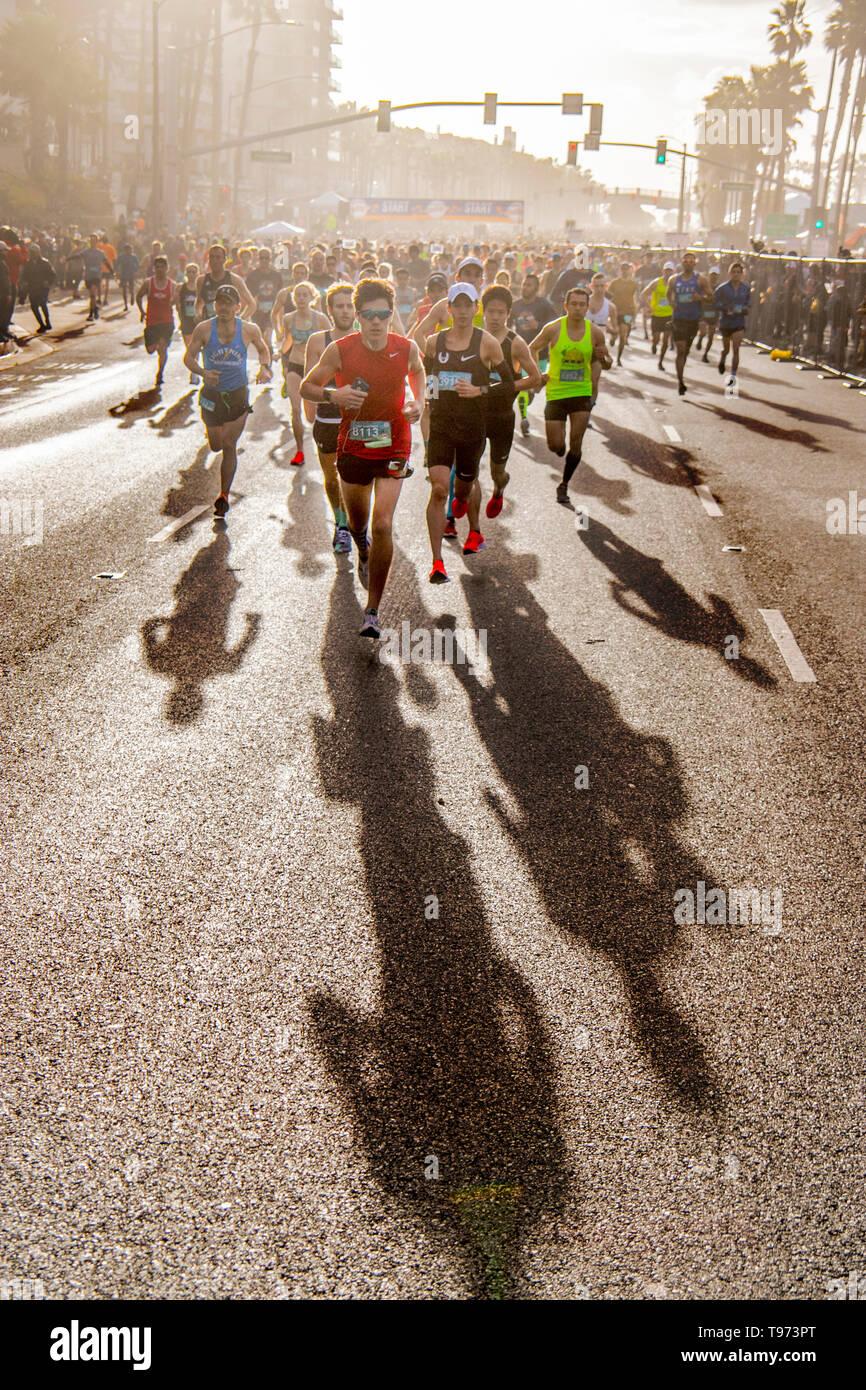 Half marathon runners throw long shadows as they leave the starting line in Huntington Beach, CA. Stock Photo