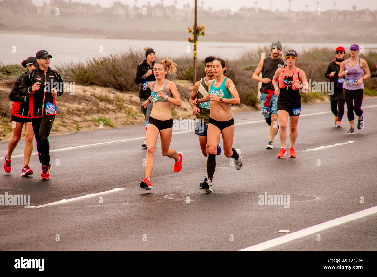 As volunteers stand by to offer assistance, female half marathon contestants run along a road in Huntington Beach, CA. - Stock Image