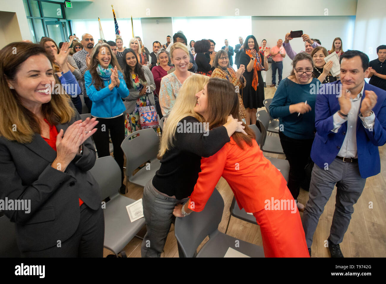 A woman politician is greeted with hugs and applause at her swearing-in for public office in Newport Beach, CA. Stock Photo