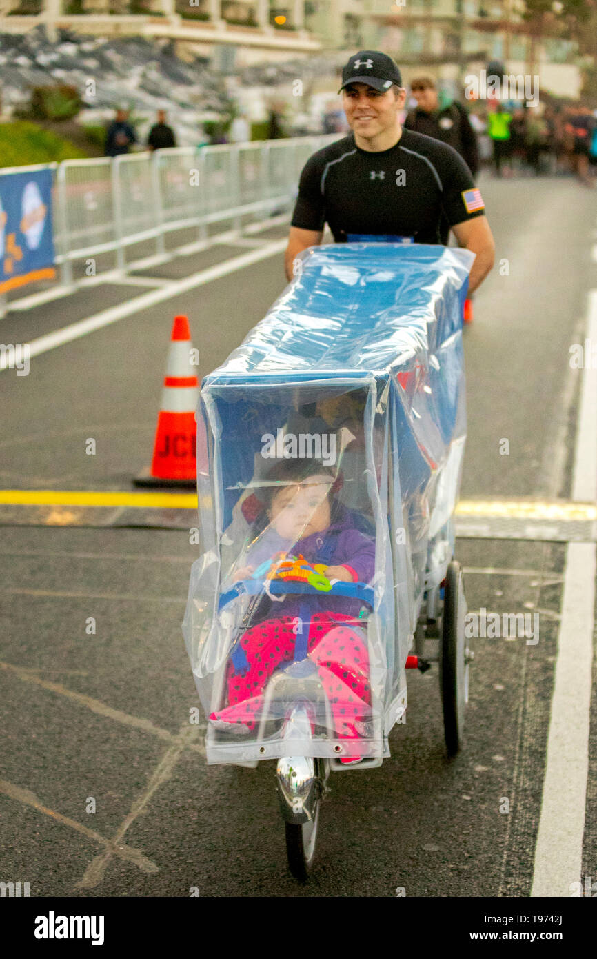 The father of quintuplets brings his children on a plastic-covered custom tricycle as he starts a marathon in Newport Beach, CA, on a rainy morning. - Stock Image