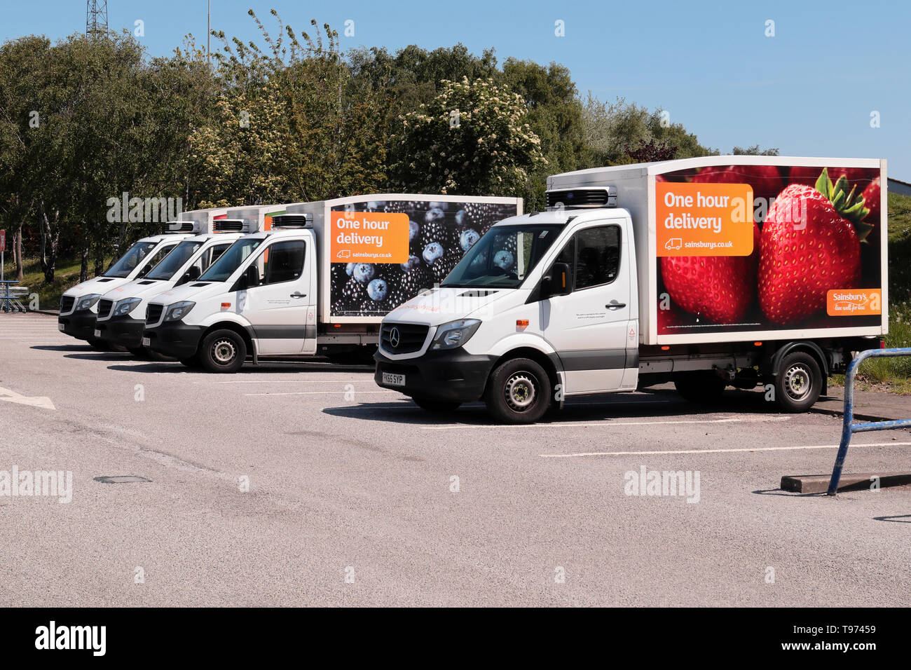 A line of four Sainsburys Home delivery Vans parked up in the store's car park. - Stock Image