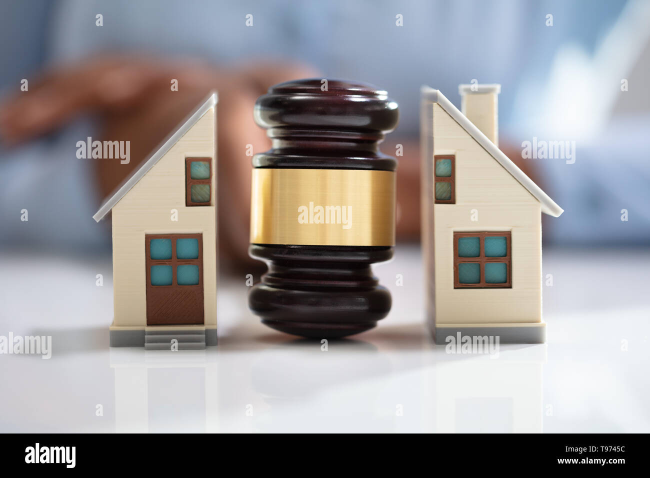 Close-up Of A Judge Striking Gavel Between Split House Over Reflective Desk - Stock Image