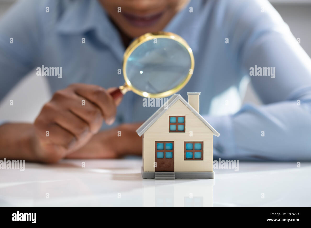 Close-up Of A Businesswoman's Hand Holding Magnifying Glass Over House Model Over Desk - Stock Image