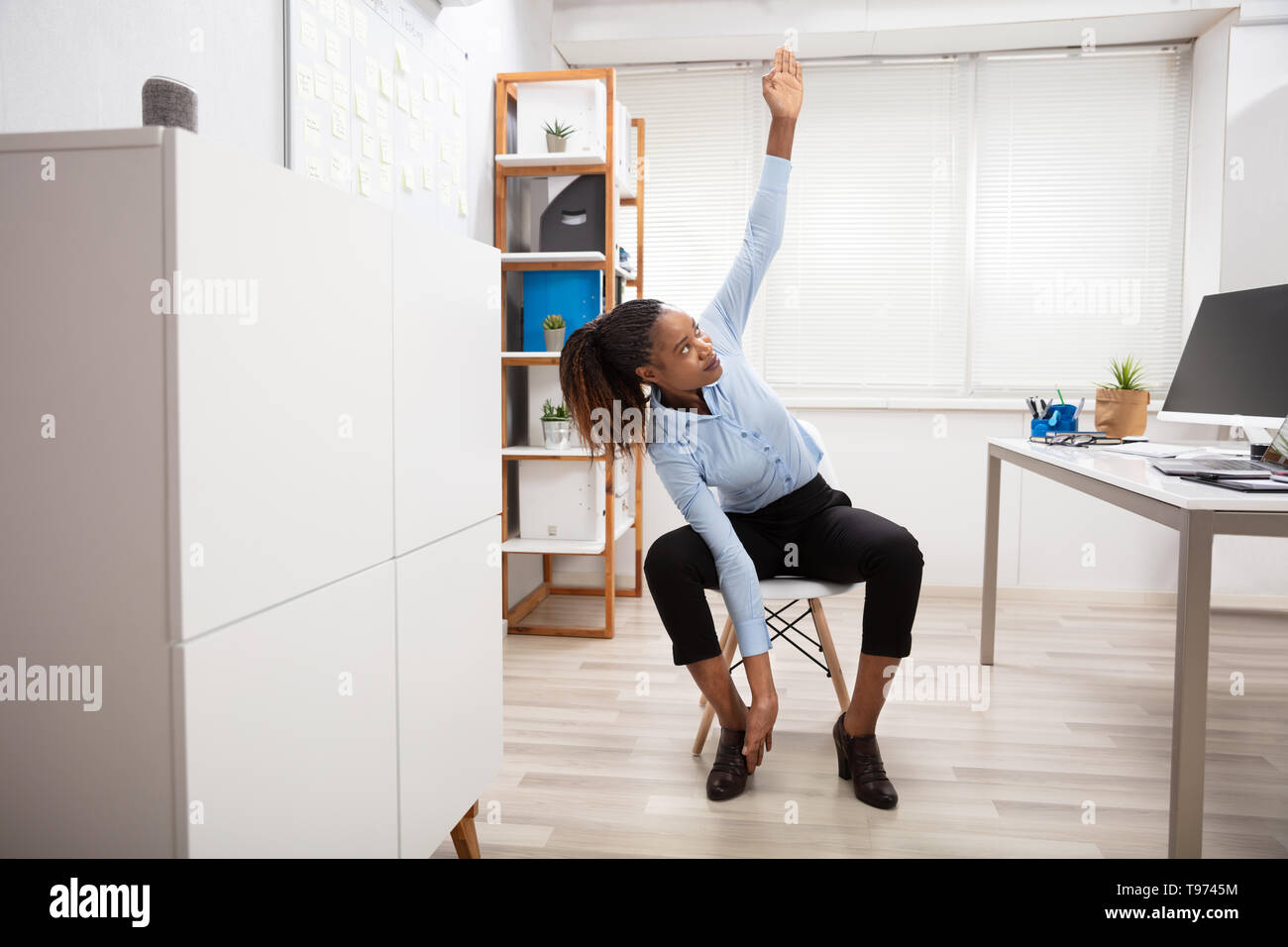Young Businesswoman Doing Yoga Standing In Front Of Office Desk Stock Photo Alamy