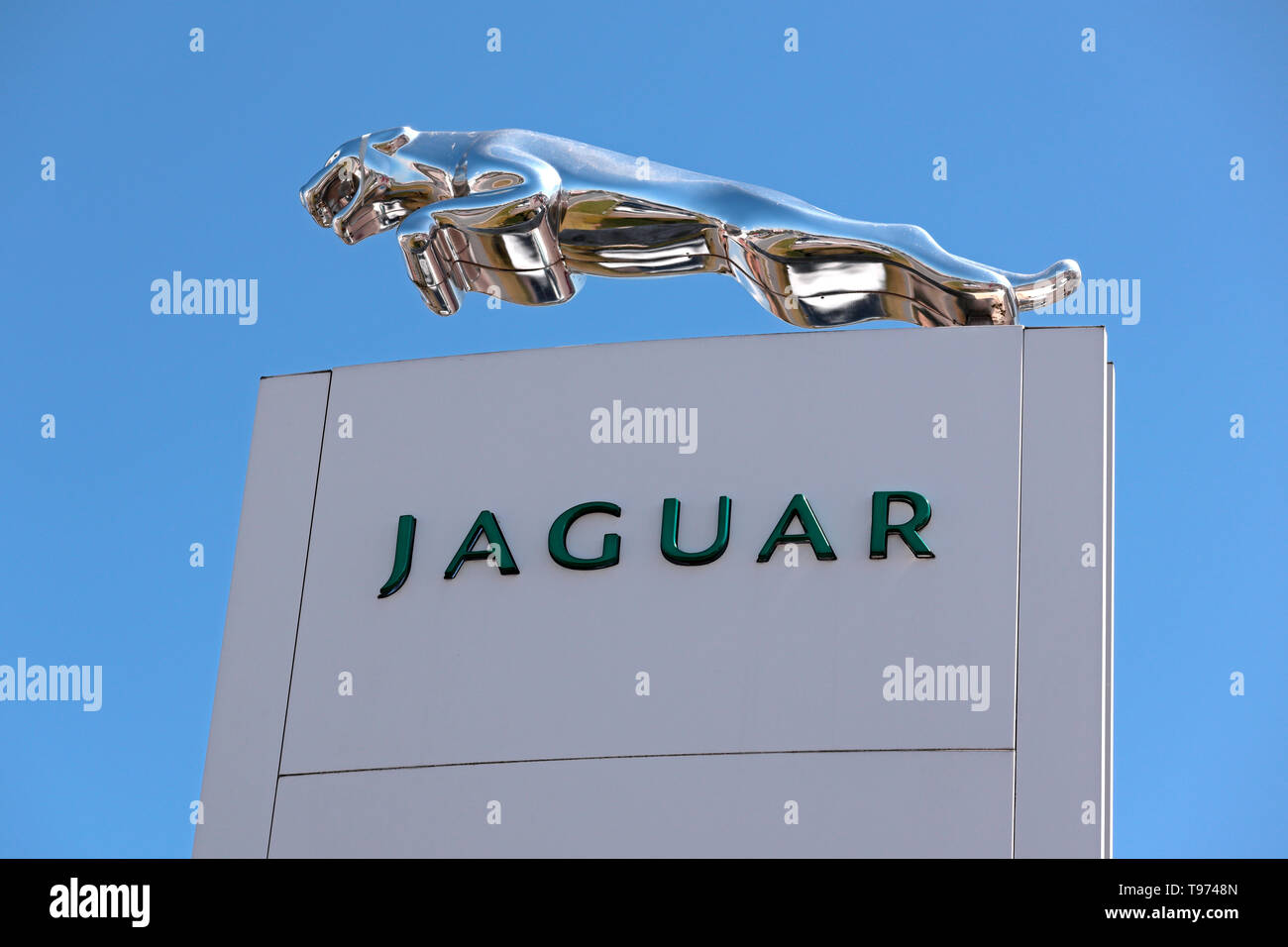 Jaguar Dealership sign with sculpted silver Jaguar Cat emblem - Stock Image
