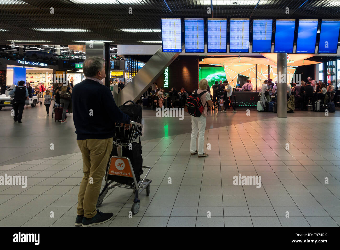 Passengers checking the departure boards in Schiphol Airport, Amsterdam, the Netherlands - Stock Image