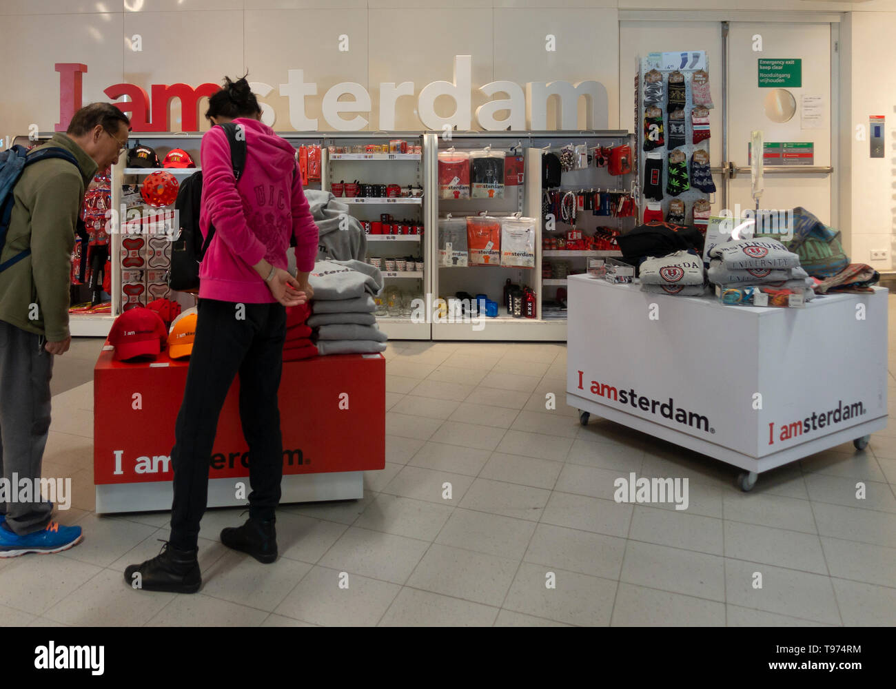 A man and a woman examining the souvenirs being sold at a retail outlet called I amsterdam in Schiphol Airport, Amsterdam, the Netherlands - Stock Image