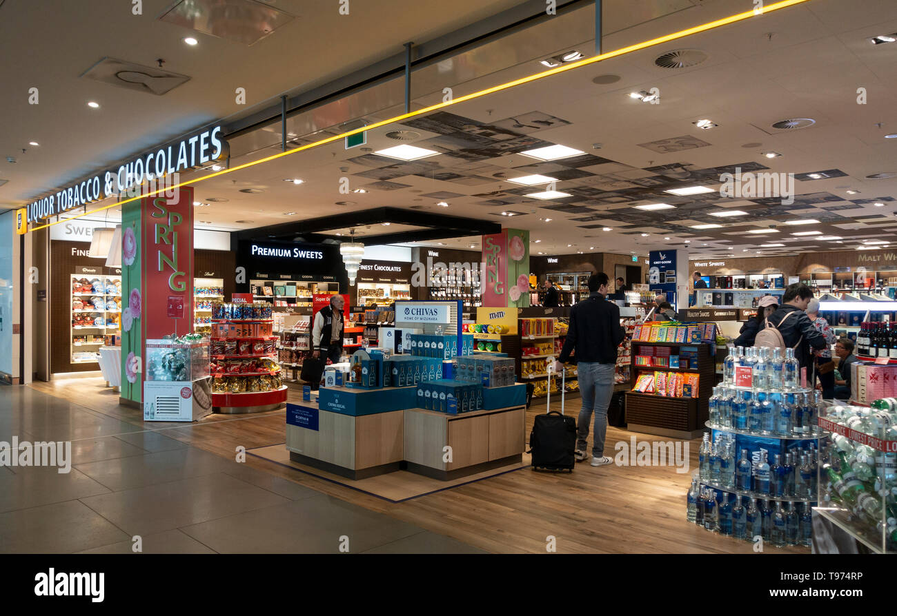 Customers in a duty-free shop selling Liquor, Tobacco and Chocolates at Schiphol Airport, Amsterdam, the Netherlands. - Stock Image