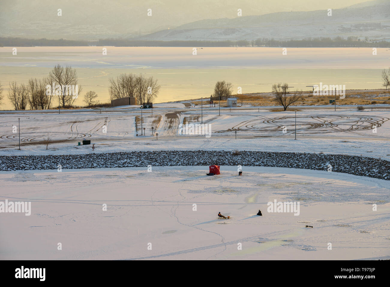 Winter Ice Fishing - On a very cold December evening, a few people are enjoying ice fishing on the frozen lake at Chatfield State Park, Colorado, USA. Stock Photo