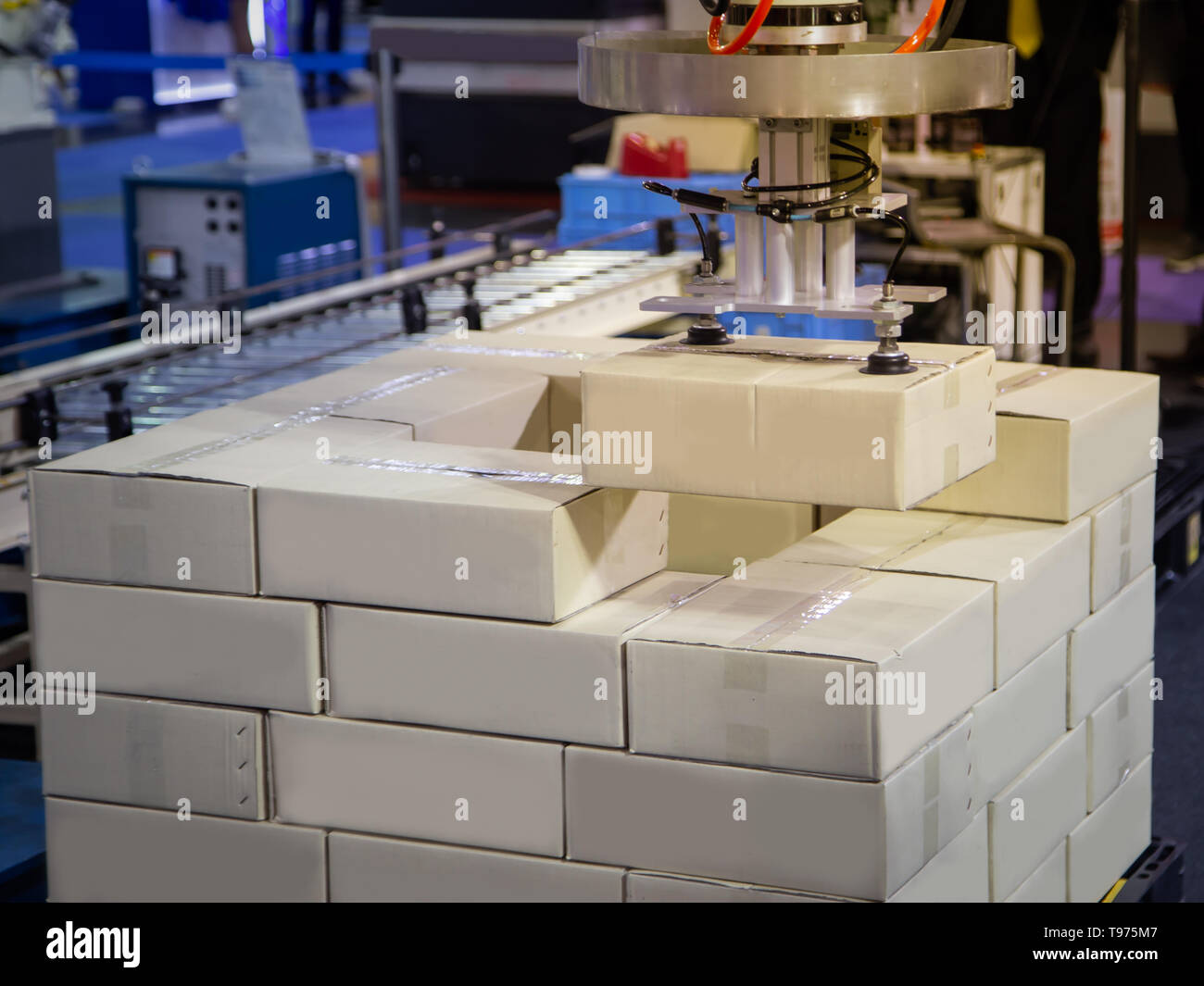 Robot arm loading carton on conveyor in manufacturing production line Stock Photo