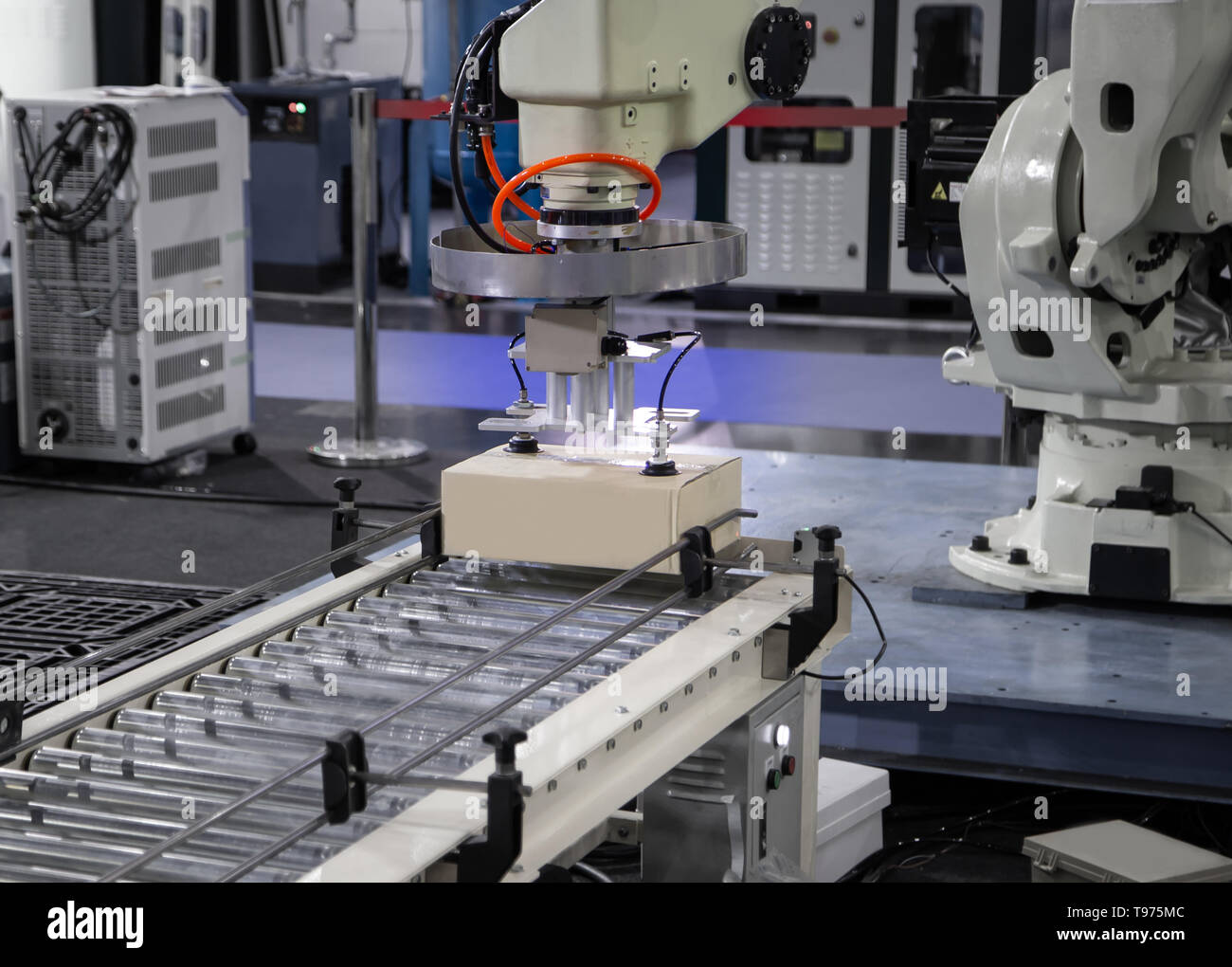 Robot arm loading carton on conveyor in manufacturing production line - Stock Image