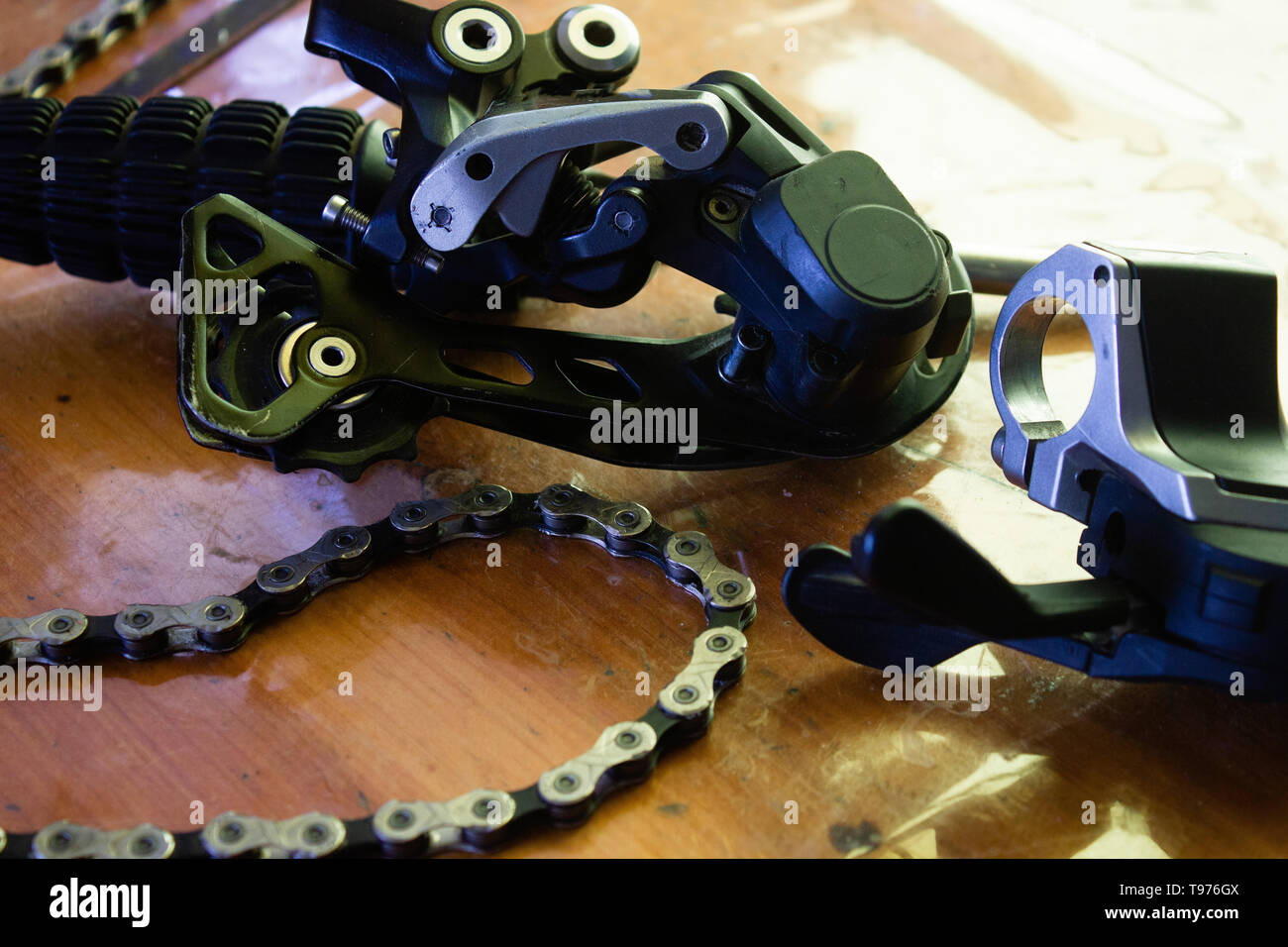 rear derailleur and chain on a wood table - Stock Image