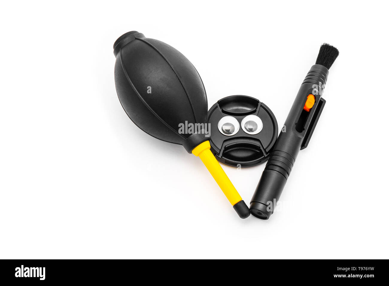 Lens Cover Face with Googly Eyes and Camera Cleaning Set Isolated on a White Background with Clipping Path. Closeup Lens Pen, Blower Brush and Lens. Stock Photo