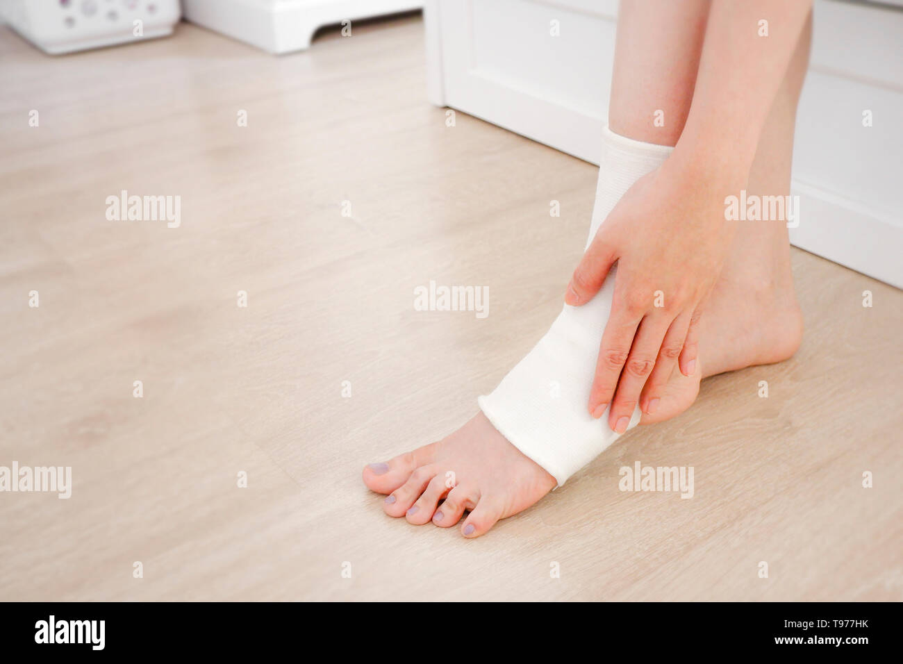 Closeup People of a Foot with White Gauze Elastic Bandage. Hands on Injured Legs and Feet on Pain Area. Asian Young Woman Ankle Injury Runner Sitting  - Stock Image