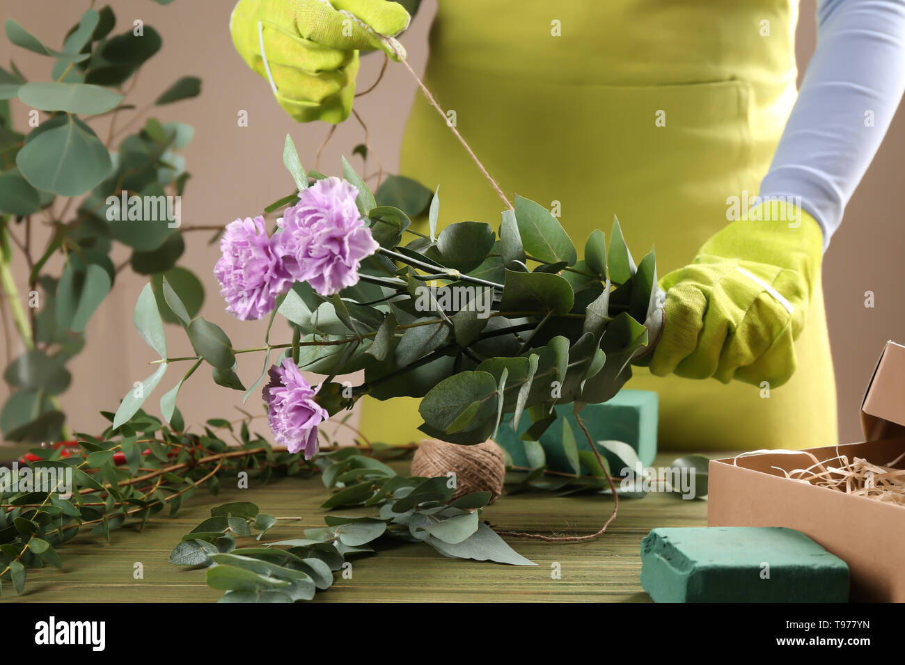 Florist making beautiful bouquet at wooden table - Stock Image