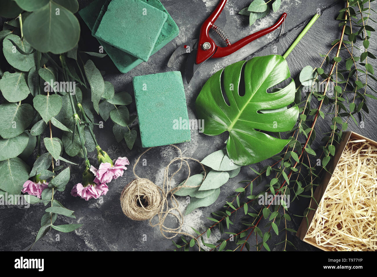 Beautiful flowers with green branches and supplies of florist on grey table - Stock Image