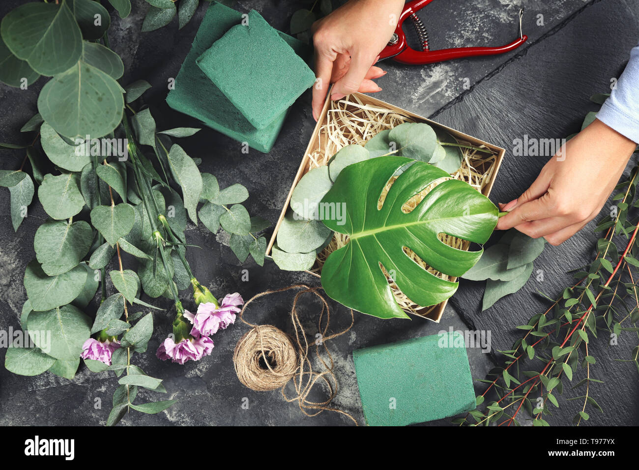 Florist preparing gift box with green branches on grey table - Stock Image