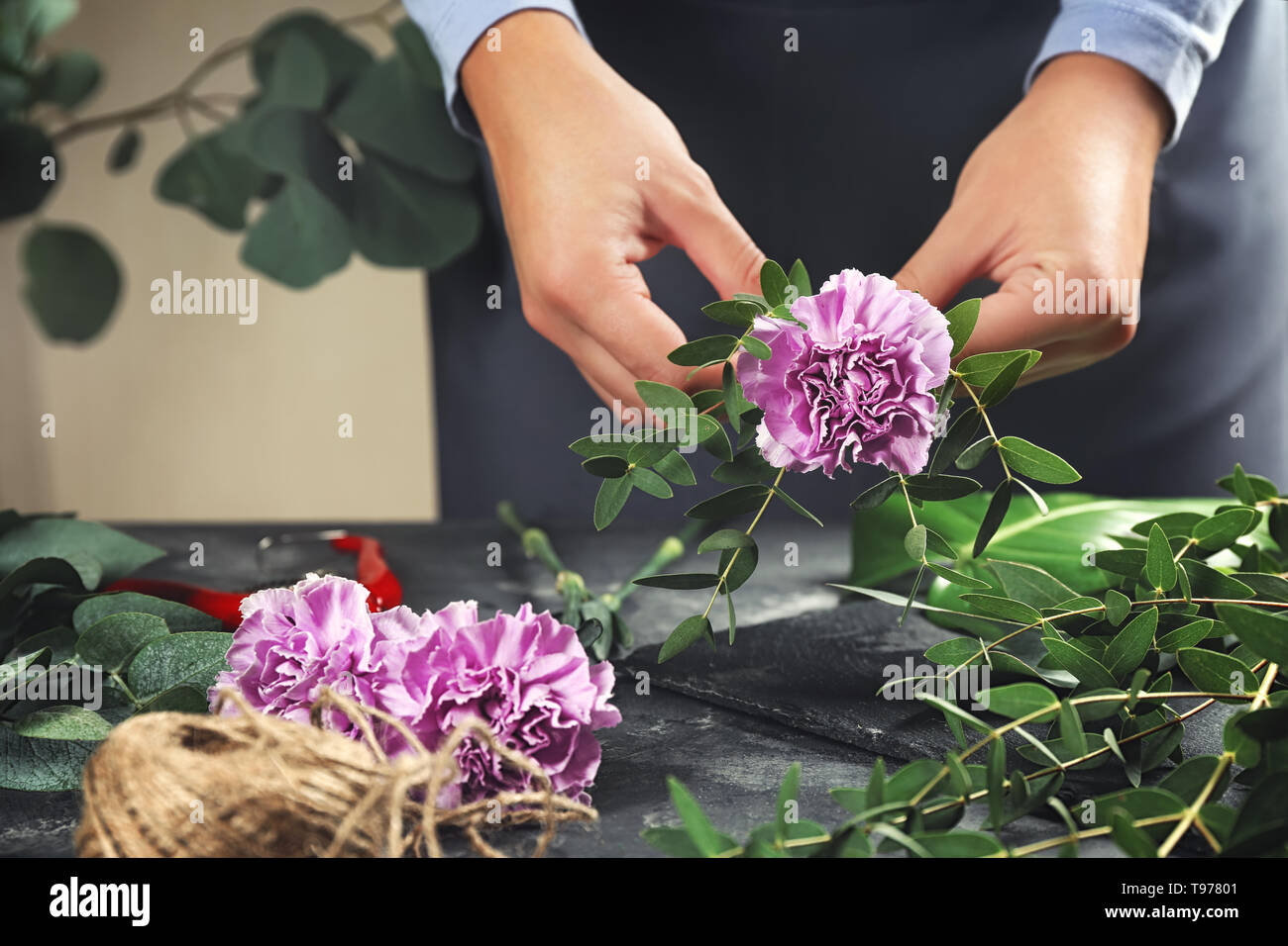 Florist making bouquet of beautiful flowers at grey table - Stock Image