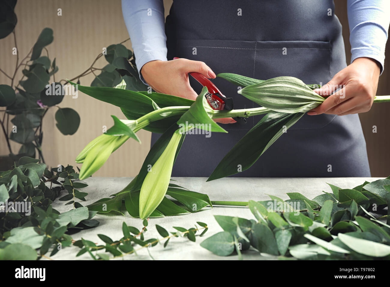Florist making beautiful bouquet at table - Stock Image
