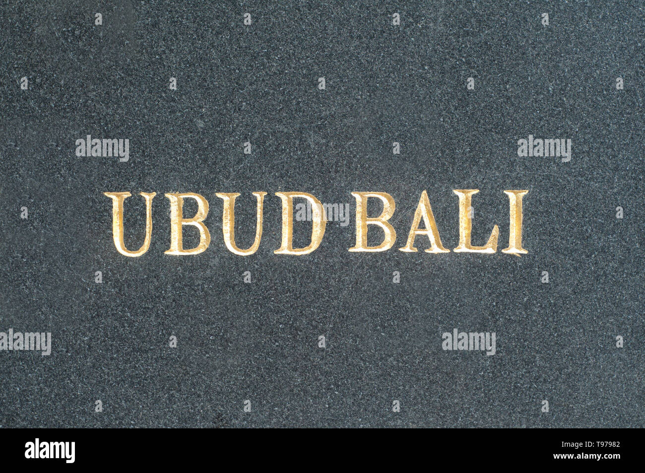 Gilded Ubud-Bali inscription on a black marble slab located in the center of Ubud, Bali, Indonesia - Stock Image
