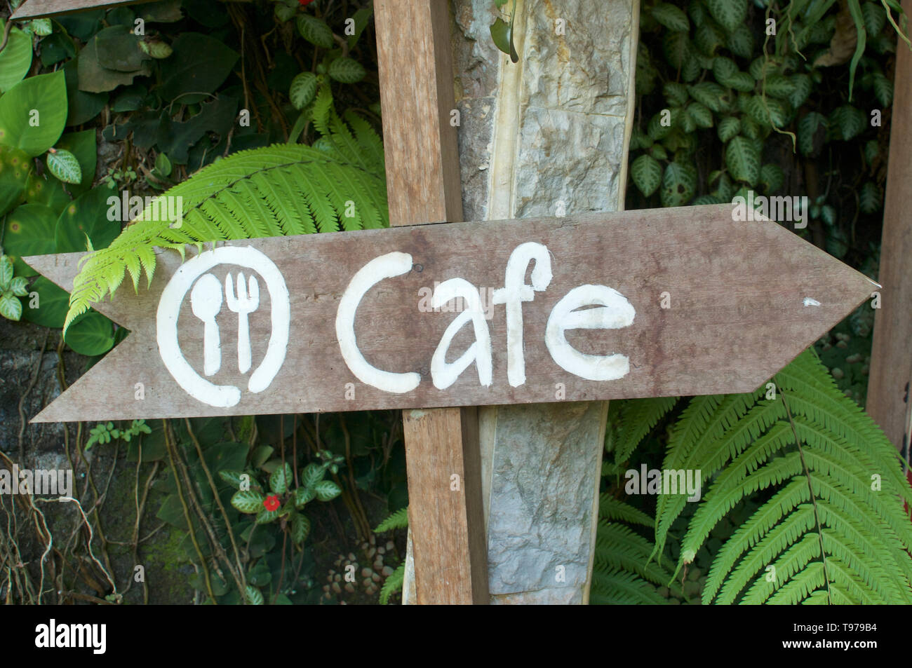White Cafe writing on a wooden arrow shaped plank, located outside a Cafe in Ubud, Bali - Stock Image