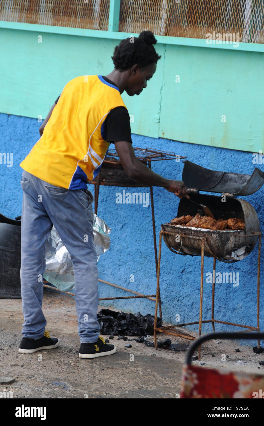 Port Antonio, Portland, Jamaica - 18th June 2017 : A Jamaican man is cooking the well known Jerk Chicken on a old rusty grill near Port Antonio in Jam - Stock Image