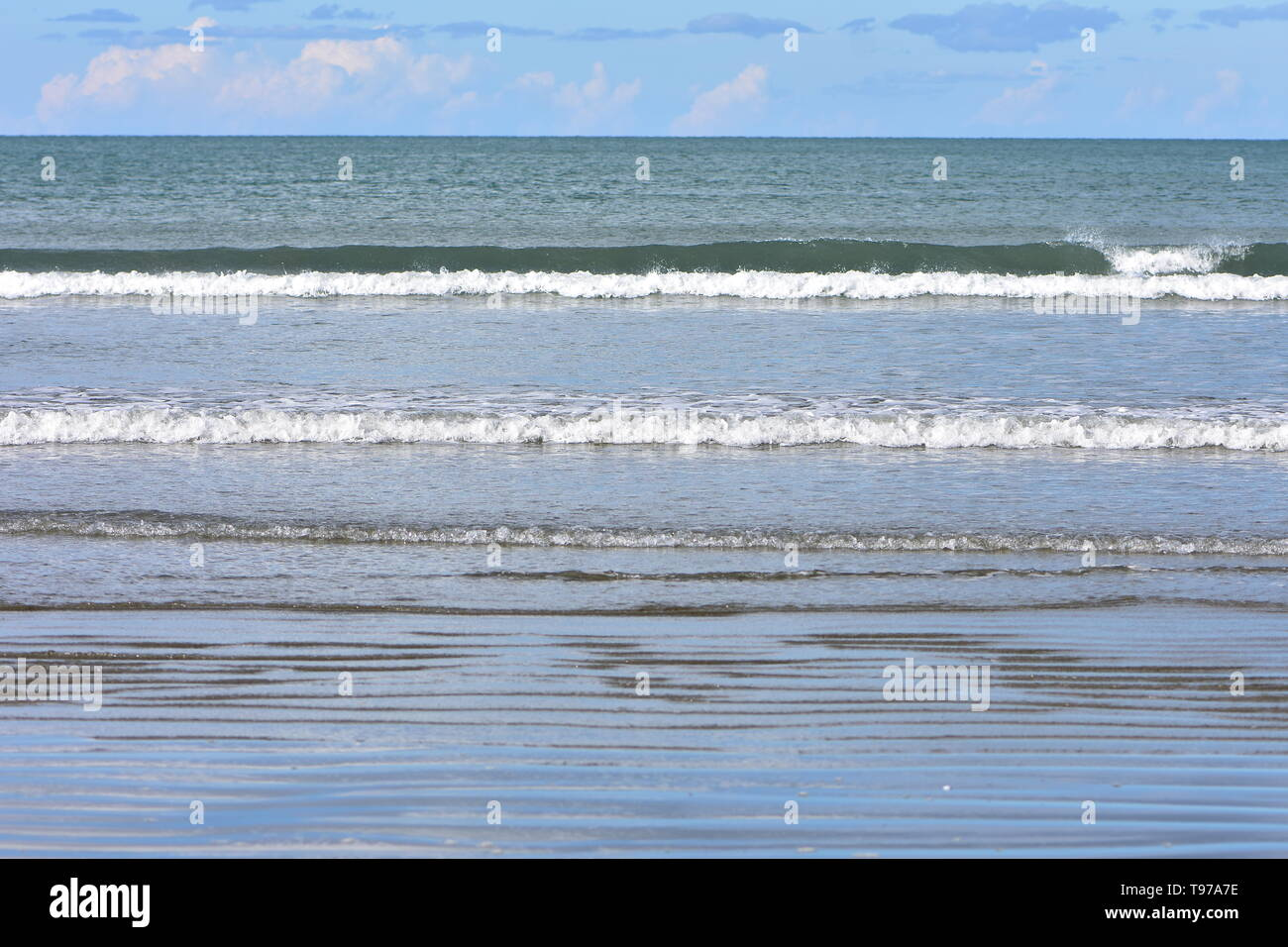 Rows of tiny surf waves rolling from calm ocean to flat sandy beach. - Stock Image
