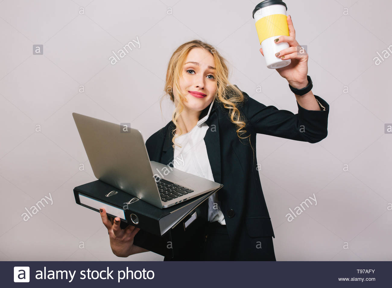 77392b682b18 Pretty blonde businesswoman with laptop, folder, box, caffee in hands  talking on phone